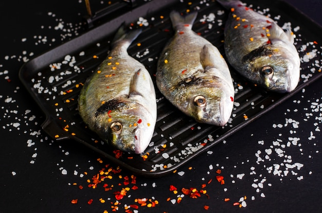 Fresh raw dorado fish on iron grill pan