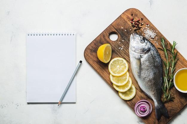 소박한 나무 커팅 보드에 신선한 생 도라도 생선과 향신료와 조리법 또는 메뉴를 위한 노트북. 흰색 배경에 상위 뷰입니다.