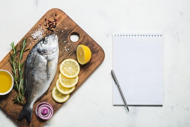 Свежая сырая рыба дорадо на деревенской деревянной разделочной доске со специями и записной книжкой для рецепта или меню. вид сверху на белом фоне.