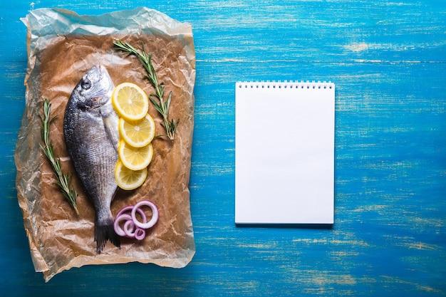 Свежая сырая рыба дорадо на кулинарной бумаге со специями и записной книжкой для рецепта или меню. вид сверху на синем фоне.