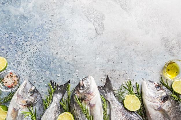 파란색 배경 위에 향신료, 허브, 레몬, 소금을 넣은 신선한 생 도라도 또는 도미