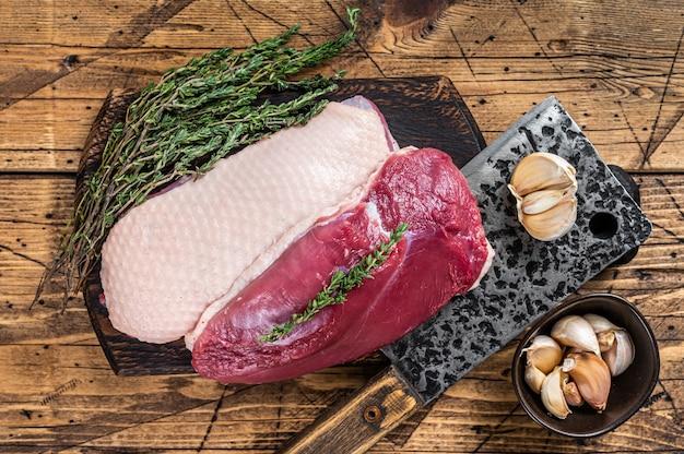 고기 식칼이 있는 정육점 보드에 신선한 생 오리 가슴살 등심 스테이크. 나무 배경입니다. 평면도.
