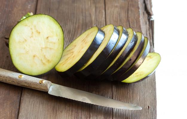 木製のテーブルにナイフで新鮮なナスのクローズアップ