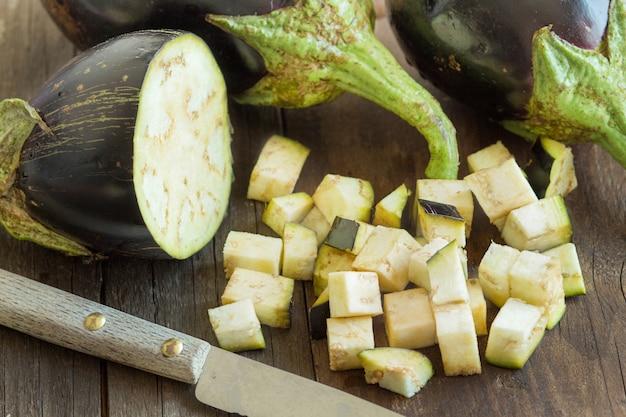 茶色の木製のテーブルにナイフで新鮮な生ナスをクローズアップ