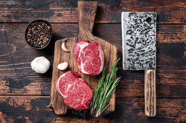 고기 식칼이 있는 정육점 커팅 보드에 신선한 생 필레 미뇽 안심 스테이크. 어두운 나무 배경입니다. 평면도.