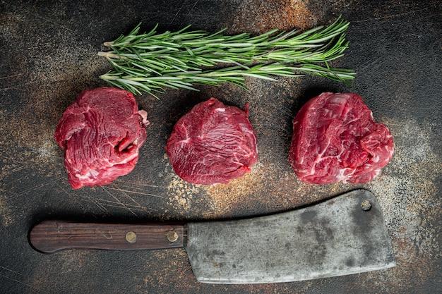 新鮮な生の切り身のミニオンステーキ、ローズマリーとニンニクのセットが付いた霜降り牛肉、古い肉屋の包丁ナイフ、古い暗い素朴な背景、上面図フラットレイ