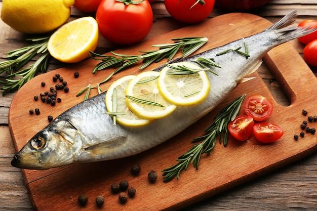 Свежая сырая рыба и пищевые ингредиенты на столе