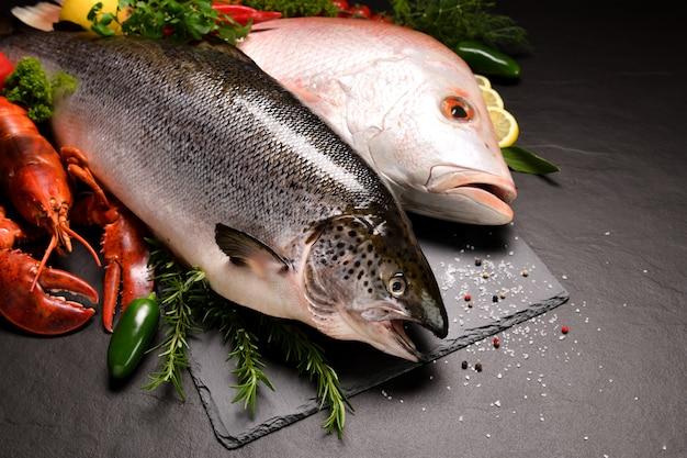 Свежая сырая рыба и морепродукты на черной каменной поверхности