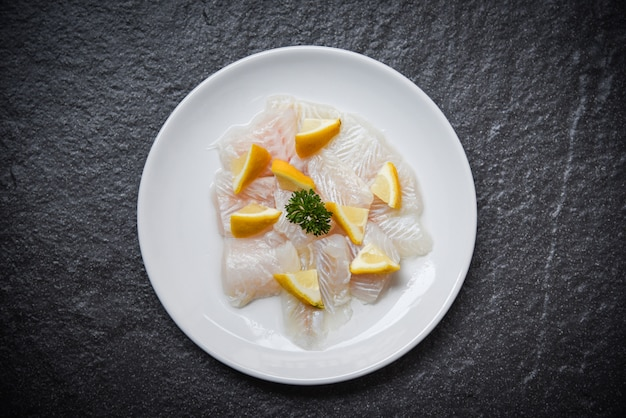 Fresh raw fish fillet piece on white plate with lemon dark background pangasius dolly fish meat