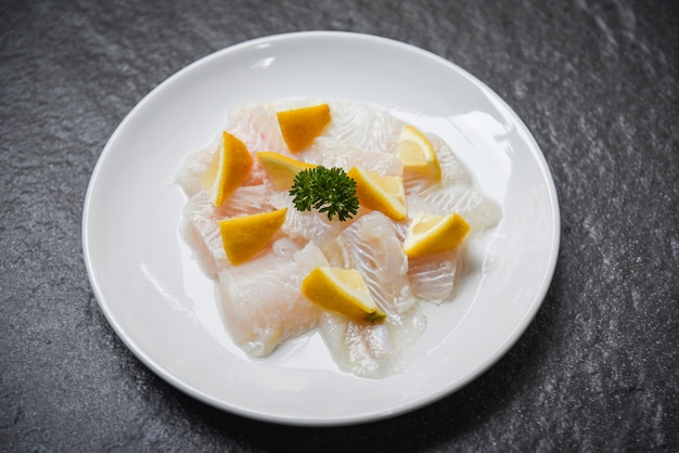 Fresh raw fish fillet piece with lemon on white plate