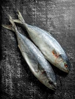 Свежая сырая рыба на темном деревенском столе