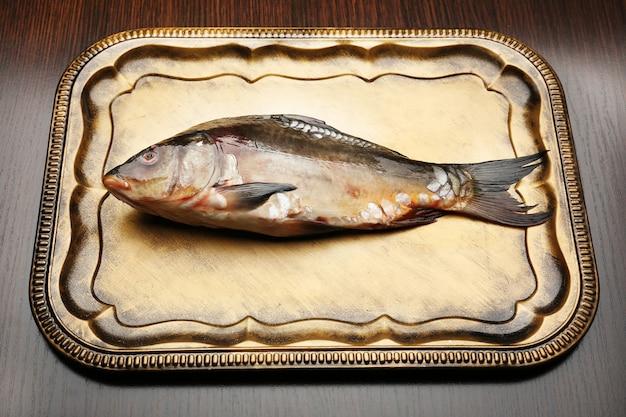 木製のテーブルのトレイに新鮮な生の魚