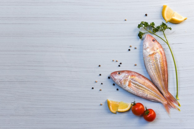 Fresh raw fish seafood with herbs and spices with lemon parsley tomato pepper seed on white wood background
