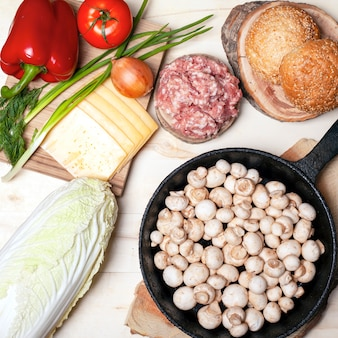Fresh raw food for burgers, buns champignon mushrooms  vegetables and meat flat lay top view.