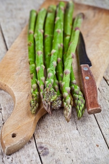 Fresh raw garden asparagus and knife closeup on cutting board