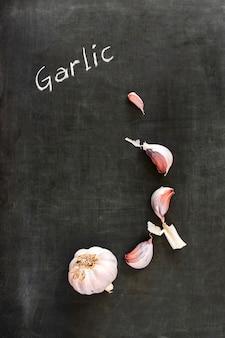 Fresh raw garlic and cloves on blackboard