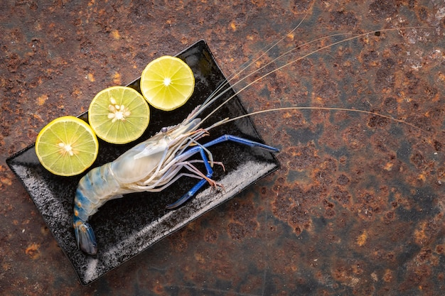 Fresh raw giant freshwater prawn in black rectangular ceramic plate with slice lime on rusty texture background with copy space for text, top view, river prawn