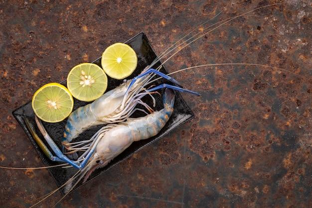 녹슨 질감 배경에 슬라이스 라임과 텍스트, 위쪽 전망, 강 새우를 위한 복사 공간이 있는 검은 직사각형 세라믹 접시에 신선한 생 거대 민물 새우