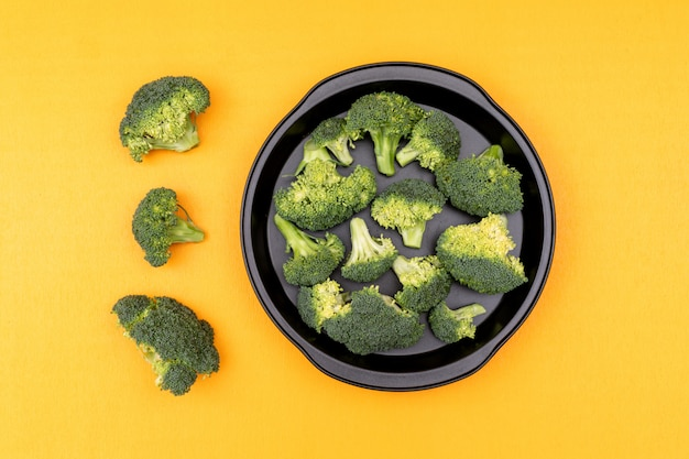 Fresh raw green broccoli in a frying pan on yellow surface