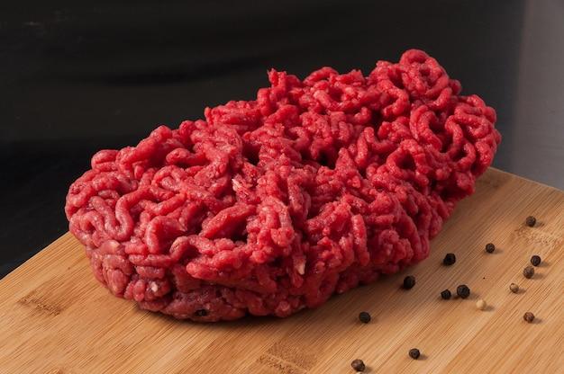 黒胡椒と木の板に新鮮な生の牛ひき肉