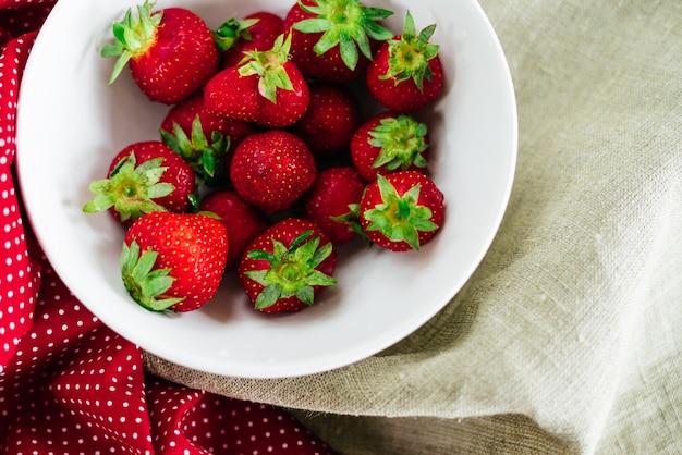 접시에 신선한 생 건강 다이어트 딸기 과일, 흰색으로 격리, 위 보기, 평평한 클로즈업, 텍스트 복사 공간, 프레임. 마을 소박한 캔버스, 시골 음식