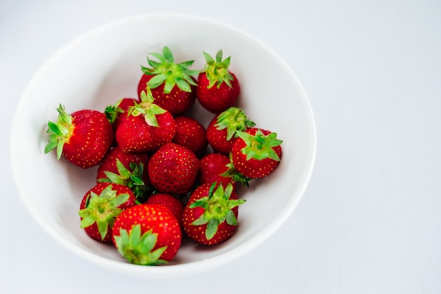 흰색으로 분리된 접시에 있는 신선한 생 건강한 다이어트 딸기 과일, 위 보기, 평평한 클로즈업, 텍스트 복사 공간, 프레임