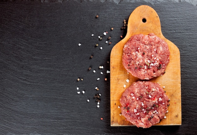 Fresh raw home-made minced beef steak burger with spices, on a cutting board on black slate table, copy space, top view