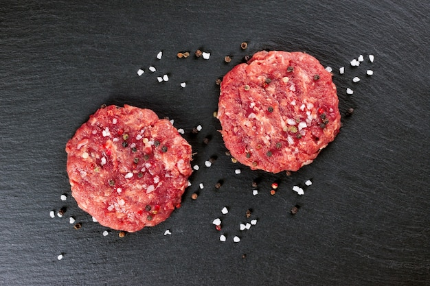 Fresh raw home-made minced beef steak burger with spices and onion, on a black slate table, top view