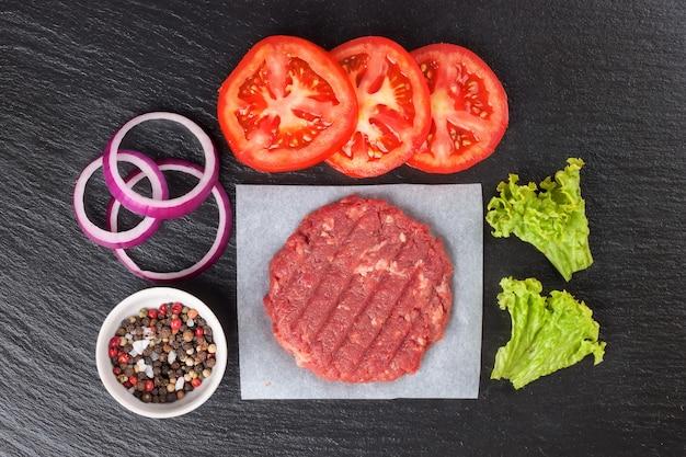 블랙 슬레이트 테이블에 향신료, 토마토, 샐러드, 양파와 신선한 원시 집에서 만든 다진 쇠고기 스테이크 햄버거, 복사 공간, 평면도