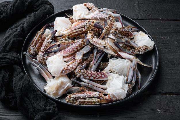 新鮮な生の馬蟹、青蟹、花蟹セット、皿、黒い木製のテーブルの上