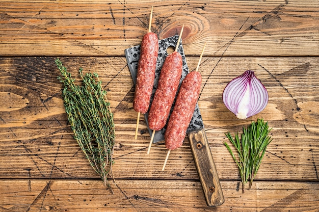 Fresh raw kofta or lula kebabs skewers on a butcher cleaver with herbs. wooden background. top view.
