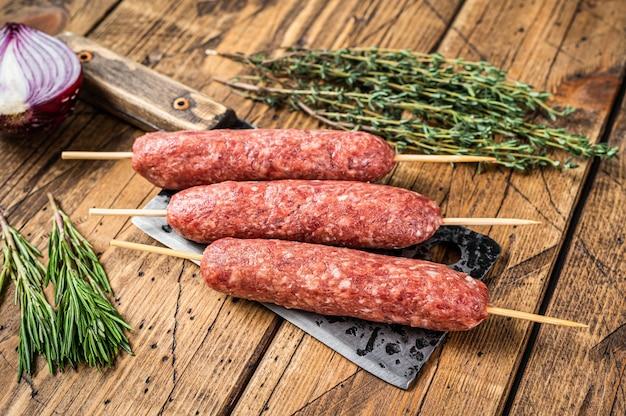 Свежая сырая кофта или люля-кебаб нанизывают на мясной нож с зеленью. деревянный фон. вид сверху.
