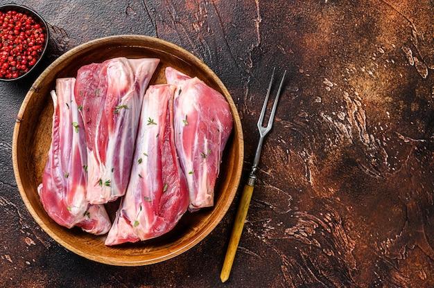 Свежее сырое мясо голени ягненка в деревянной тарелке. темный фон.