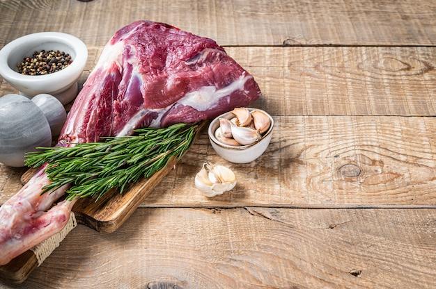 Свежая сырая баранина или козья ножка с розмарином и перцем на разделочной доске