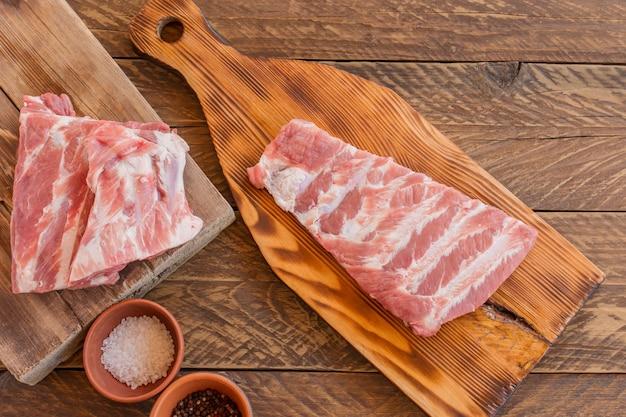 향신료와 허브를 곁들인 신선한 생 양고기 갈비. 나무 배경입니다. 평면도.