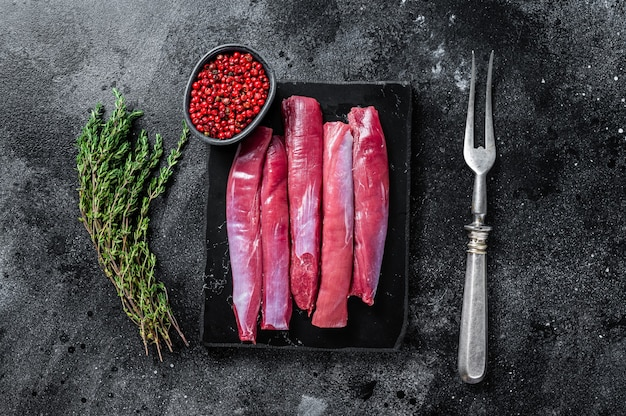 신선한 생 양고기 안심 필레, 백리향이 있는 대리석 판에 양고기 등심 고기. 검은 배경. 평면도.