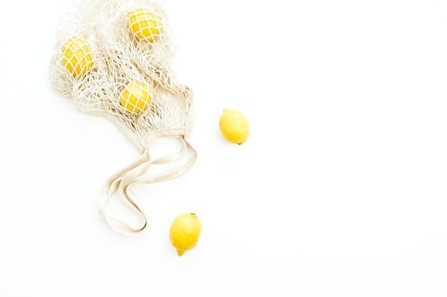 Свежие сырые лимоны в авоське. плоская планировка, вид сверху концепция цитрусовых
