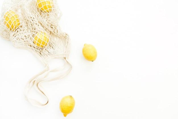 Свежие сырые лимоны в авоське на белом фоне. плоская планировка, вид сверху