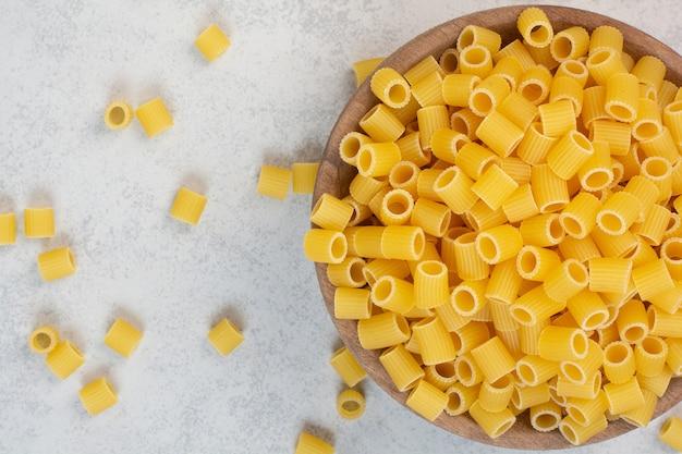 Свежие сырые макароны на деревянной тарелке.