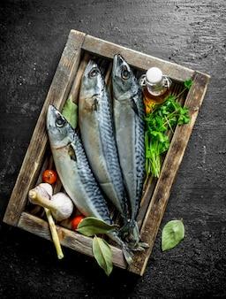 パセリとニンニクと木製のトレイに新鮮な生のサバ。黒の素朴なテーブルの上