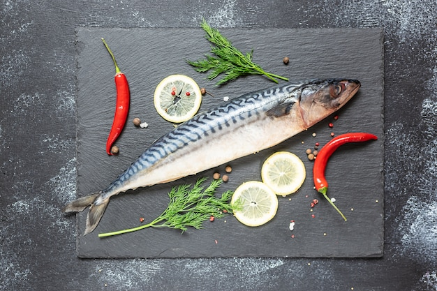 Fresh raw mackerel with spices and vegetables on black stone board top view.
