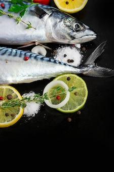Fresh raw mackerel with tomato and lemon on a black metal pan.