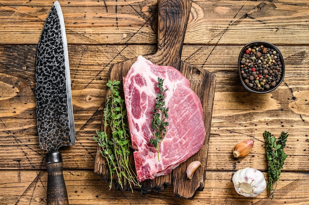 ナイフでまな板の上に新鮮な生の霜降り肉のポークステーキ。木製の背景。上面図。