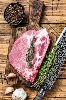 Свежие сырые мраморные стейки из свинины на разделочной доске с ножом