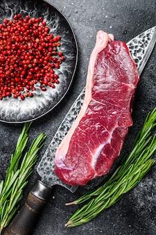 Fresh raw marbled beef meat sirloin steak on a knife