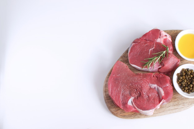Fresh raw meat beef steak olive oil spices pepper rosemary
