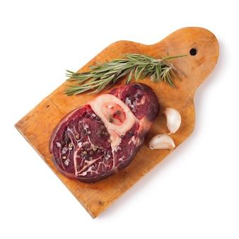白い背景で隔離の木製まな板にスパイス、ローズマリー、ニンニク、オリーブオイルと骨付きの新鮮な生肉ビーフステーキ。上面図。フラットレイ。
