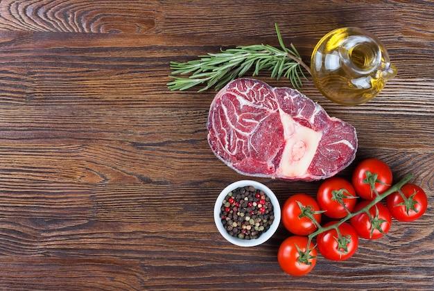Стейк из свежего сырого мяса из говядины с косточкой со специями, помидорами розмарином и оливковым маслом