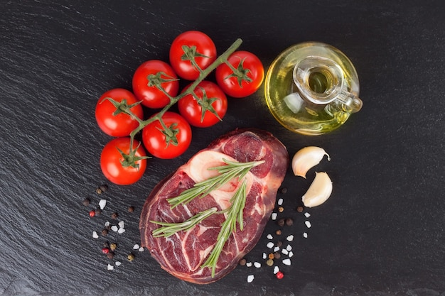 Fresh raw meat beef steak with bone with spices, rosemary, tomatoes and olive oil on the black slate surface. cooking ingredients. top view. flat lay.