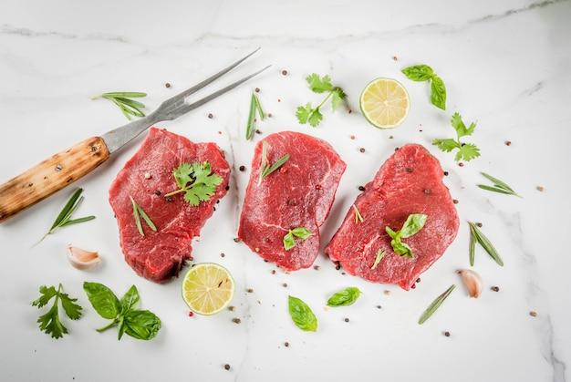 Свежее сырое мясо. говяжья вырезка, стейки, на белом мраморном столе. с оливковым маслом, специями для приготовления пищи - базиликом, розмарином, кориандром, петрушкой, чесноком, лимоном, солью, перцем. скопировать вид сверху